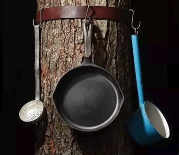 belt over tree to hold pots and pans on campsite