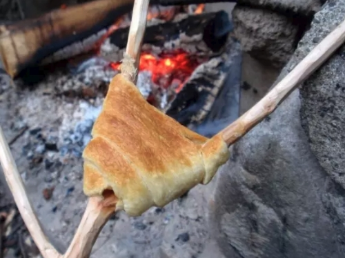 cook dough on stick over campfire