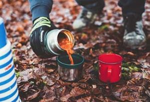 camper pouring hot soup into a bowl from a thermos container in the campsite