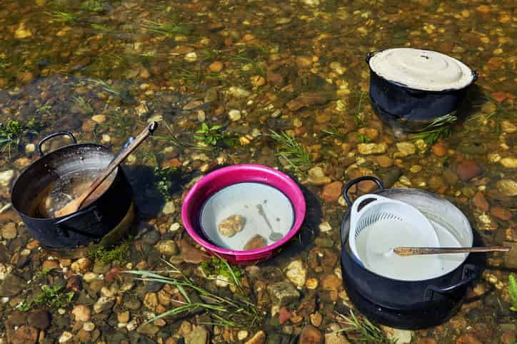dirty camping cookware in a river in the middle of the cleaning process