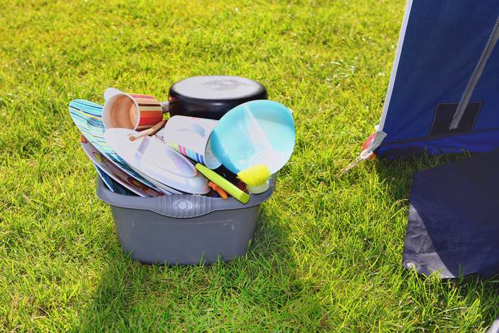 pile of dirty dishes next to a tent on a camping trip