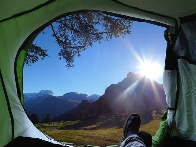 open camping tent overlooking a mountain and nature