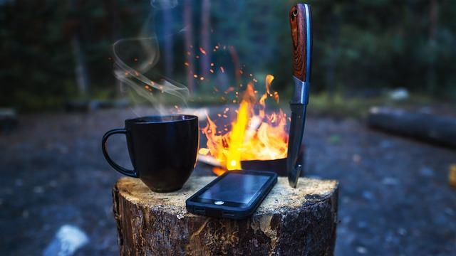 camping knife, mug, and phone on a log over a campfire