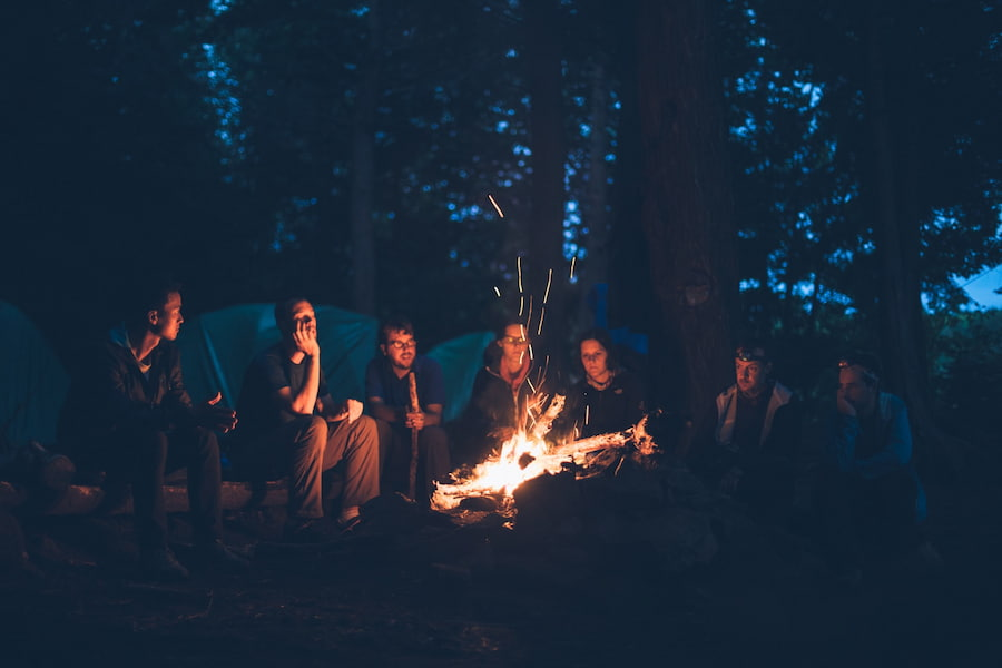 people hanging over a campfire