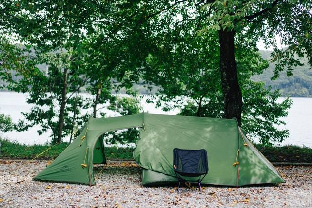green tent under the shade of a tree